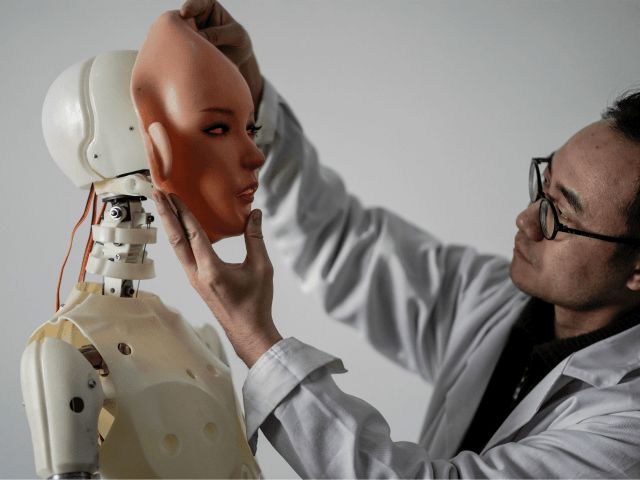 TOPSHOT - This photo taken on February 1, 2018 shows an engineer holding a silicon face against the head of a robot at a lab of a doll factory of EXDOLL, a firm based in the northeastern Chinese port city of Dalian. With China facing a massive gender gap and …