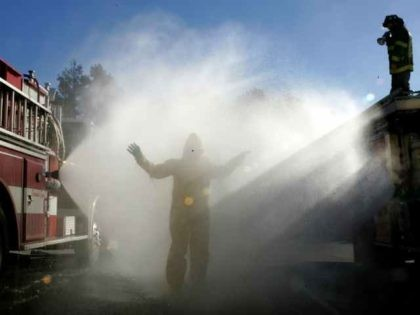 Hazmat team getting washed off by fire truck