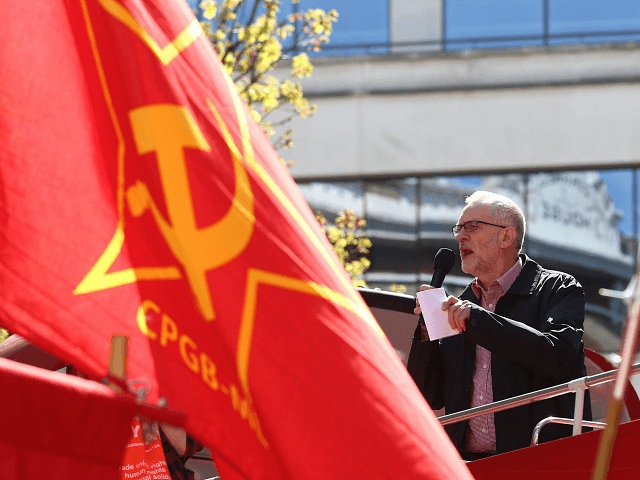 Britain's opposition Labour Party leader Jeremy Corbyn gives a speech from the top of a double-decker bus as Communist Party of Great Britain (Marxist-Leninist) flags fly at a May Day rally in London on May 1, 2016. / AFP / JUSTIN TALLIS (Photo credit should read JUSTIN TALLIS/AFP/Getty Images)
