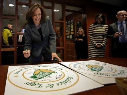 Democratic presidential candidate Sen. Kamala Harris, D-Calif., signs posters at a Politics & Eggs campaign event, Tuesday, Feb. 19, 2019, in Manchester, N.H. (AP Photo/Elise Amendola)