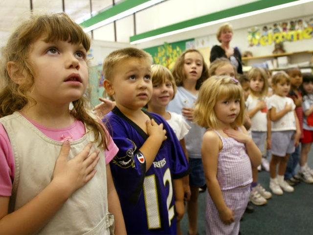 Sarah Henderson (L) and children from Mrs. Morrow's kindergarden class at Sunderland Elementry school recite the Pledge of Allegiance September 17, 2002 in Sunderland, Maryland.