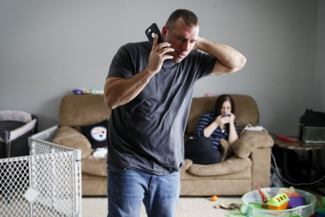 In this Nov. 28, 2018 photo, Tom Wolikow, a General Motors employee who is currently laid-off, left, takes a phone call at home alongside his fiance Rochelle Carlisle, right, in Warren, Ohio. It was working-class voters who bucked the area's history as a Democratic stronghold and backed Donald Trump in …