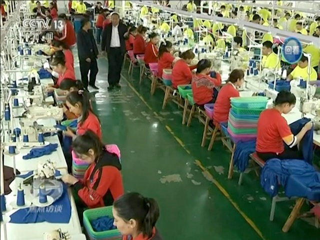 In this file image from undated video footage run by China's CCTV via AP Video, Muslim trainees work in a garment factory at the Hotan Vocational Education and Training Center in Hotan, Xinjiang, northwest China. A U.S. company that stocks college bookstores with t-shirts and other team apparel cut ties …
