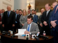 Oklahoma Gov. Kevin Stitt signs the permitless carry bill into law, as legislators look on, Wednesday, Feb. 27, 2019, in Oklahoma City.