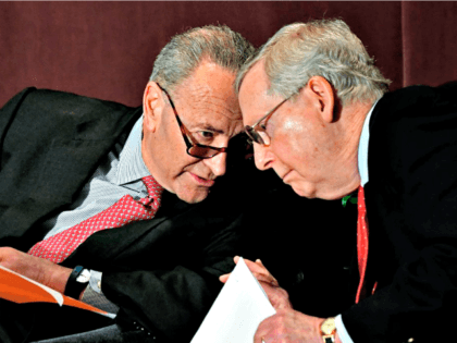Senate Minority Leader Charles Schumer, D-N.Y., left, leans in to speak to Senate Majority Leader Mitch McConnell, R-Ky., before his speech at the McConnell Center's Distinguished Speaker Series Monday, Feb. 12, 2018, in Louisville, Ky. (AP Photo/Timothy D. Easley