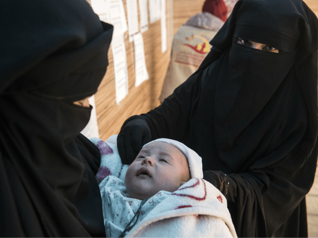 Displaced Syrian women hold a child as they wait at a makeshift clinic at the Internally Displaced Persons (IDP) camp of al-Hol in al-Hasakeh governorate in northeastern Syria on February 7, 2019. (Photo by FADEL SENNA / AFP) (Photo credit should read FADEL SENNA/AFP/Getty Images)
