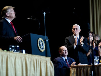 US Senator Christopher Coons (Seated), US Vice President Mike Pence (C), and others clap for US President Donald Trump during the National Prayer Breakfast on February 7, 2019 in Washington, DC. (Photo by Brendan Smialowski / AFP) (Photo credit should read BRENDAN SMIALOWSKI/AFP/Getty Images)