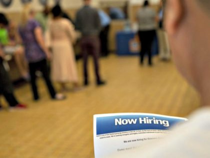 The U.S. has added jobs in every month for nearly eight years. Here, a job seeker holds an employment flyer during a hiring event at an Aldi Supermarket in Darien, Ill., in July. Daniel Acker/Bloomberg via Getty Images