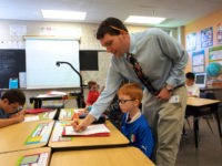 Christian Buzzerd, a teacher at Triadelphia Ridge Elementary School in Ellicott City, Maryland, helps a pupil write in cursive on Octber 15, 2013.