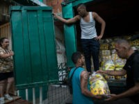 "Neighbors download subsidized food distributed under a government program named ""CLAP,"" in the Catia district of Caracas, Venezuela, Thursday, Jan. 31, 2019. An independent U.N. human rights monitor says economic sanctions are compounding a ""grave crisis"" in Venezuela."
