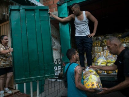 """Neighbors download subsidized food distributed under a government program named """"CLAP,"""" in the Catia district of Caracas, Venezuela, Thursday, Jan. 31, 2019. An independent U.N. human rights monitor says economic sanctions are compounding a """"grave crisis"""" in Venezuela."""