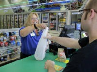 A cashier, left, makes a sale to Nicholas Scott, of Chicopee, Mass., right, at the Pride Station & Store, Thursday, Aug. 24, 2017, in Chicopee, where the winning ticket for the Powerball was sold. (AP Photo/Steven Senne)