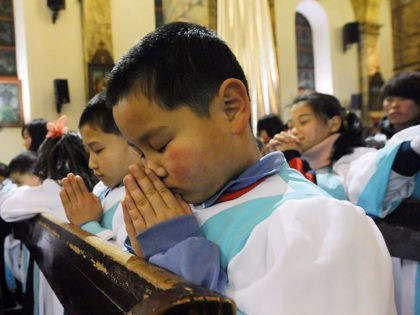 This picture taken on December 24, 2012 shows young Chinese congregation members praying during the Christmas Eve mass at a Catholic church in Beijing. While China does not officially celebrate Christmas, its popularity continues to grow with non-Christians keen to see and feel the experience of Christmas. AFP PHOTO / …