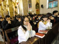 This picture taken on December 24, 2012 shows Chinese congregation members praying during the Christmas Eve mass at a Catholic church in Beijing. While China does not officially celebrate Christmas, its popularity continues to grow with non-Christians keen to see and feel the experience of Christmas. AFP PHOTO / WANG …