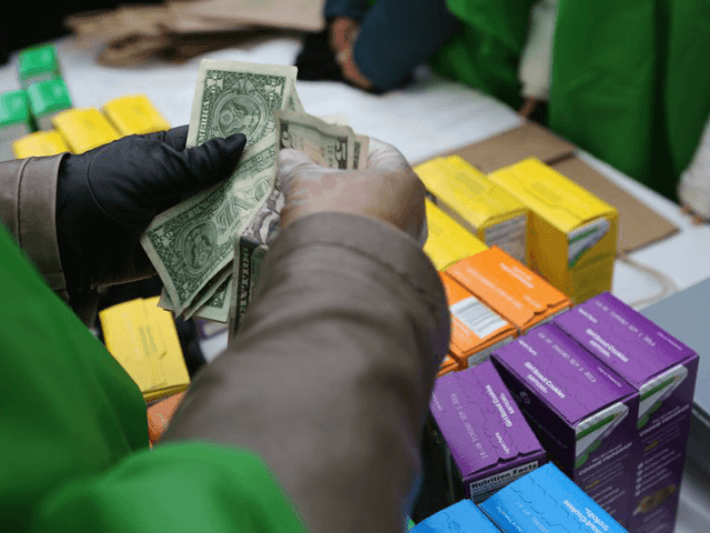 NEW YORK, NY - FEBRUARY 08: MOney is collected as Girl Scouts sell cookies while a winter storm moves in on February 8, 2013 in New York City. The scouts did brisk business, setting up shop in locations around Midtown Manhattan on National Girl Scout Cookie Day. (Photo by John …