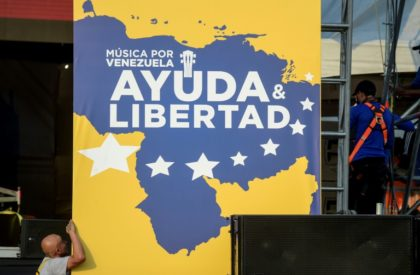 Workers set up posters for a charity concert for the Venezuelan opposition
