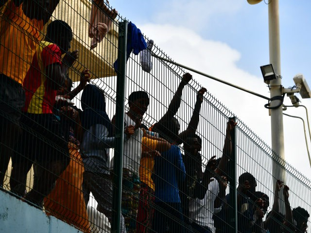 Migrants inside the Centre for Temporary Stay of Immigrants (CETI) cheers towards newly arrived African migrants which successfully breached the border from Morocco into the Spanish exclave of Ceuta on August 22, 2018 in Ceuta, Spain. This morning 100-150 mostly sub-saharan refugees crossed the barb wire fence from Morocco into …