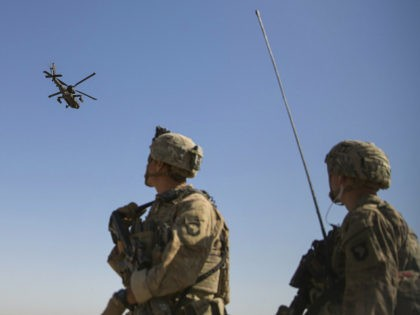 This June 10, 2017 photo released by the U.S. Marine Corpsshows an AH-64 Apache attack helicopter provides security from above while CH-47 Chinooks drop off supplies to U.S. Soldiers with Task Force Iron at Bost Airfield, Afghanistan. Sixteen years into its longest war, the United States is sending another 4,000 …