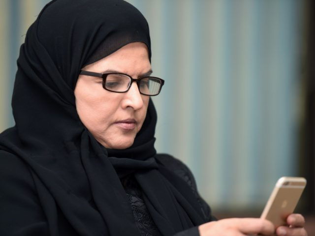 Saudi activist and campaigner Aziza al-Yousef checks her mobile phone during an interview in the capital Riyadh, on September 27, 2016. Thousands of Saudis have signed a petition urging an end to the guardianship system giving men control over the work, study, marriage and travel of female relatives, activists said. …