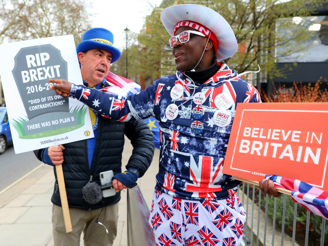 TOPSHOT - Anti-Brexit campaigner Steve Bray (L) talks with pro-Brexit supporter Joseph Afrane as they walk near the Houses of Parliament in London on March 13, 2019. - British MPs will vote Wednesday on whether the country should leave the EU without a deal in just over two weeks, after …