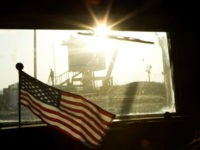 A border guard stands on Iraq's border with Kuwait behind a US flag fluttering on the dashboard of a Mine Resistant Ambush Protected (MRAP) vehicle from the 3rd Brigade Combat Team, 1st Cavalry Division as the last US convoy leaves Iraq on December 18, 2011.