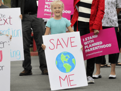 A young girl with a sign concerning global warming joined about 200 demonstrators before a town hall meeting with Republican US Representative Darrell Issa at a high school in San Juan Capistrano, California, June 3, 2017. / AFP PHOTO / Bill Wechter (Photo credit should read BILL WECHTER/AFP/Getty Images)