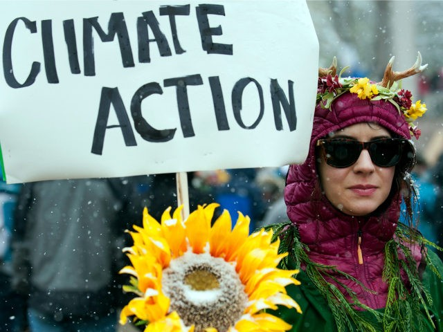 Beth Phuxster of Denver, Colorado, dressed as Mother Nature, holds a sign while participating in the People's Climate March during a spring snow storm in Denver, Colorado on April 29, 2017. (Photo by Jason Connolly / AFP) (Photo credit should read JASON CONNOLLY/AFP/Getty Images)