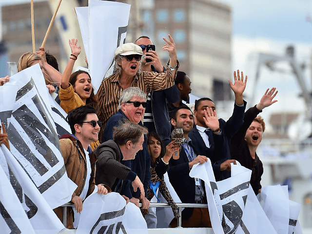 A boat carrying supporters for the Remain in the EU campaign including Bob Geldof (C) shout and wave at Brexit fishing boats as they sail up the river Thames in central London on June 15, 2016. A Brexit flotilla of fishing boats sailed up the River Thames into London today …