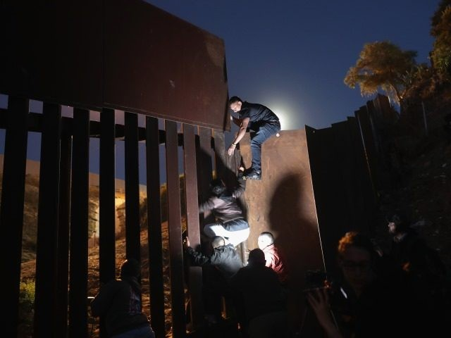 Migrants scale outdated border barrier in San Diego Sector. (File Photo: John Moore/Getty Images)