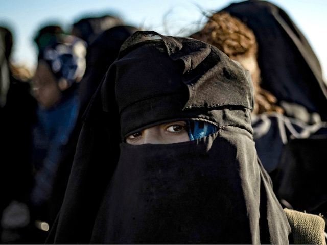 A woman looks on as she waits to be searched by members of the Kurdish-led Syrian Democratic Forces (SDF) after leaving the Islamic State (IS) group's last holdout of Baghouz, in the eastern Syrian Deir Ezzor province on March 1, 2019. - Kurdish-led forces launched a final assault Friday on …