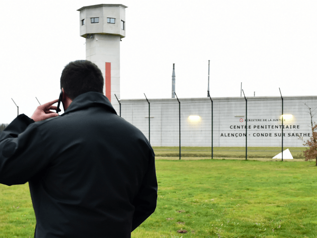 A member of the 'Regional Response and Security Teams' (ERIS), who replaces staff members on strike, speaks on the telephone as prison guards block the entrance to the penitentiary center of Alencon, in Conde-sur-Sarthe, northwestern France, on early March 6, 2019, a day after a prison inmate seriously wounded two …