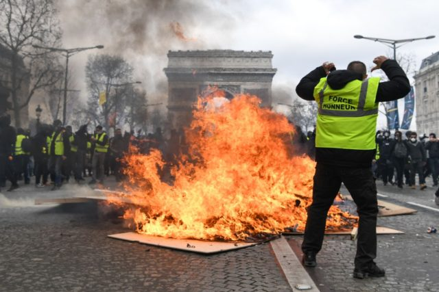 TOPSHOT - A Yellow Vest protester gestures behind flames rising from a barricade, in Paris on March 16, 2019, during the 18th consecutive Saturday of demonstrations called by the 'Yellow Vest' (gilets jaunes) movement. - Demonstrators hit French city streets again on March 16, for a 18th consecutive week of …