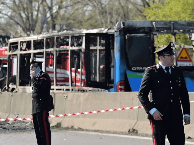 Itaian policemen work by the wreckage of a school bus that was transporting some 50 children on March 20, 2019 after it was torched by the bus' driver, in San Donato Milanese, southeast of Milan. - Italian police rescued some 50 children on March 20, 2019 after their driver threatened …