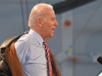 "US Vice President Joe Biden takes off his military jacket before delivering a speech at the ""90 Military Airbase"" in Bucharest on May 20, 2014. US Vice President Joe Biden blasted Russia's annexation of Crimea, saying borders should not be changed at gunpoint, as he began a visit to Romania …"