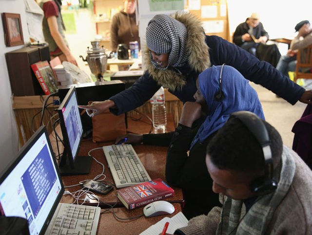"BAD BELZIG, GERMANY - OCTOBER 26: Warda Abdi (standing), 23, an asylum-seeker from Somalia, looks at a YouTube video with her friend and fellow-Somali asylum applicant Asha at the ""Der Winkel"" cafe where many local asylum applicants go for Internet access and company on October 26, 2015 in Bad Belzig, …"