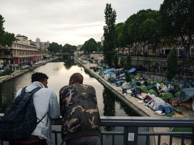 TOPSHOT - Men look at a makeshift camp during its evacuation by police, along the Canal de Saint-Martin at Quai de Valmy in Paris, on June 4, 2018. - More than 500 migrants and refugees were evacuated on early June 4, 2018 from a makeshift camp that had been set …
