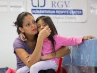"A woman from Honduras and her 4-year-old daughter seeking asylum sit at a Catholic Charities relief center on Sunday, June 17, 2018 in McAllen, Texas. - People went to the center for assistance after being released from detention through ""catch and release"" immigration policy. (Photo by Loren ELLIOTT / AFP) …"