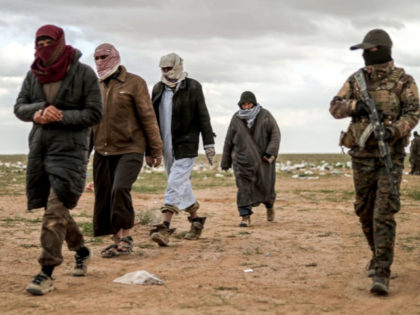 Men suspected of being an Islamic State (IS) group's fighter walk next to a member of the Kurdish-led Syrian Democratic Forces (SDF) as they wait to be searched after leaving the IS group's last holdout of Baghouz, in Syria's northern Deir Ezzor province on February 27, 2019.