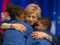 Gov. Janet Mills hugs two young singers during her inauguration ceremony, Wednesday, Jan. 2, 2019, at the Augusta Civic Center in Augusta, Maine. Mills, a Democrat, is the state's first female governor. (AP Photo/Robert F. Bukaty)