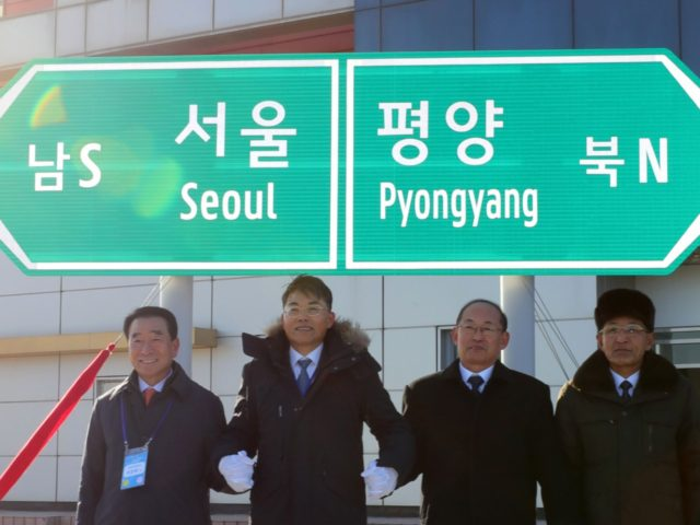 KAESONG, NORTH KOREA - DECEMBER 26: Officials from South and North Korea stand in front of a road sign during the ceremony for a project to modernize and connect roads and railways over the border between the Koreas at Panmun Station on December 26, 2018 in Kaesong, North Korea. South …
