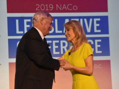 Greg Cox, president of the National Association of Counties, thanks Kellyanne Conway, senior adviser to President Donald Trump, for speaking at the organization's annual legislative conference in Washington, DC, on Monday.