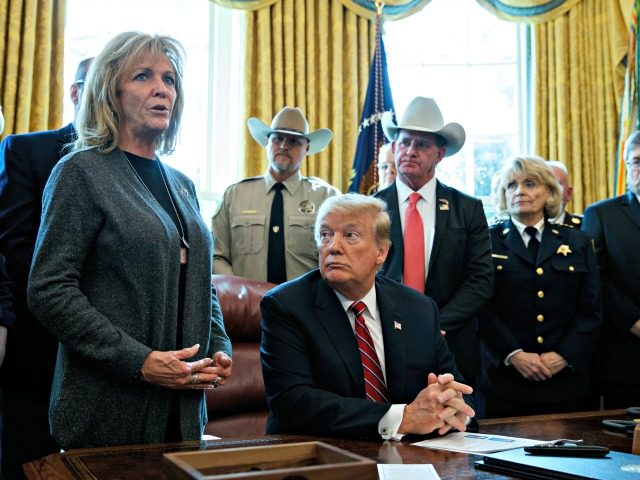 "President Donald Trump listens as Mary Ann Mendoza, an ""Angel Mom"" who lost her son Brandon when he was killed by a drunk driver that was an undocumented immigrant, speaks before he signs the first veto of his presidency in the Oval Office of the White House, Friday, March 15, …"
