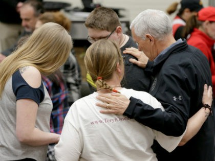 Vice President Mike Pence, right, prays with members of a family from Fremont, Neb., who were displaced by the recent floods, at a shelter in the Elkhorn Middle School, in Omaha, Neb., Tuesday, March 19, 2019. (AP Photo/Nati Harnik)