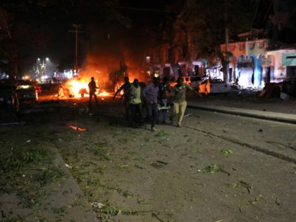 Rescuers run as they carry a stretcher in Mogadishu, the capital of Somalia, on February 28, 2019 after a car bomb exploded close to a major hotel killing at least five people and wounding 25 others. - Witnesses described how the blast ripped through one of the busiest streets of …
