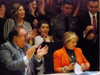 Democratic New Mexico Gov. Michelle Lujan Grisham, sitting right, signs a bill into law that expands background checks to nearly all gun sales in New Mexico in a ceremony in in Santa Fe, N.M., Friday, March 8, 2019.