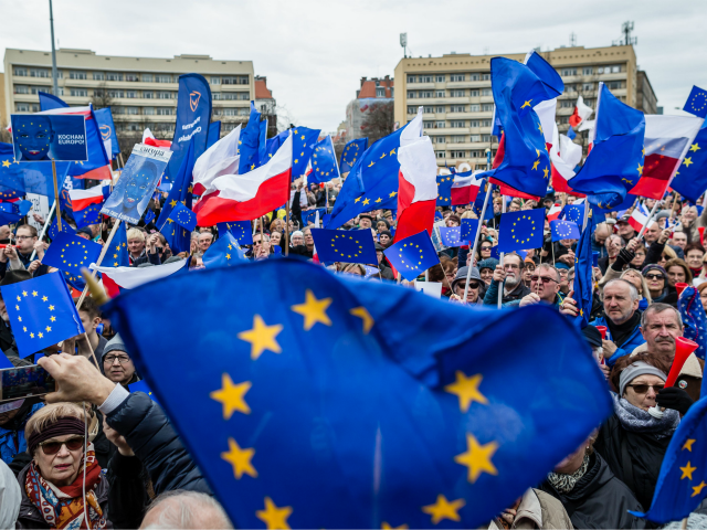 People wave EU and Polish flags during a demonstration of the Committee for Democracy Defence (KOD), in Warsaw, on March 25, 2017, to mark the 60th anniversary of the Rome treaty. / AFP PHOTO / Wojtek RADWANSKI (Photo credit should read WOJTEK RADWANSKI/AFP/Getty Images)