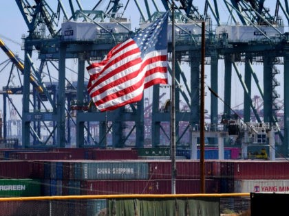 The US flag flies over Chinese shipping containers that were unloaded at the Port of Long Beach, in Los Angeles County, on September 29, 2018. - President Donald Trump insisted that there had been 'absolutely no impact' on the US economy from the escalating trade dispute between his administration and …