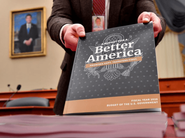 A Senate staff member displays a copy of volume one of President Trump's fiscal year 2020 budget as they are delivered to the House Budget Committee on Capitol Hill on Monday. Photo by Kevin Dietsch/UPI