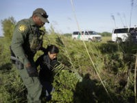 FILE - In this Aug. 11, 2017, file photo a U.S. Customs and Border Patrol agent escorts an immigrant suspected of crossing into the United States illegally along the Rio Grande near Granjeno, Texas. The U.S. government posted a seventh straight monthly increase in people being arrested or denied entry …