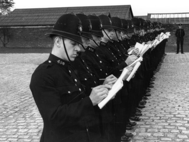 8th November 1938: Recruits of the Lancashire Constabulary, being trained at Stanley Grange, Houghton, near Preston, take notes during a staged smash and grab raid, as part of a general intelligence test. (Photo by Fox Photos/Getty Images)